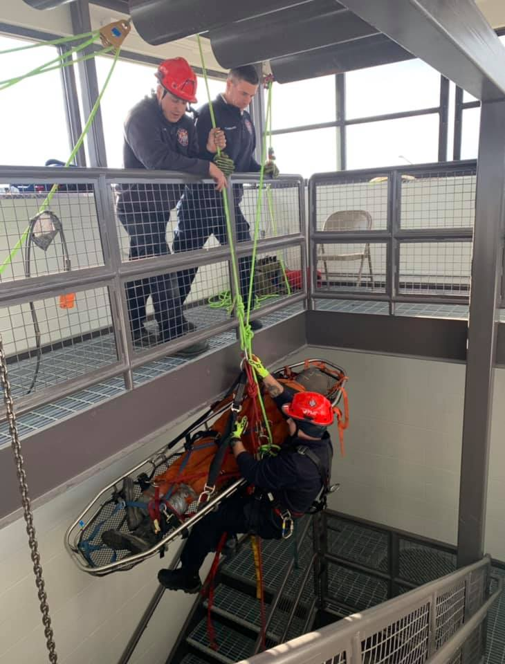 Firefighter being lowered in basket in tower during training exercise