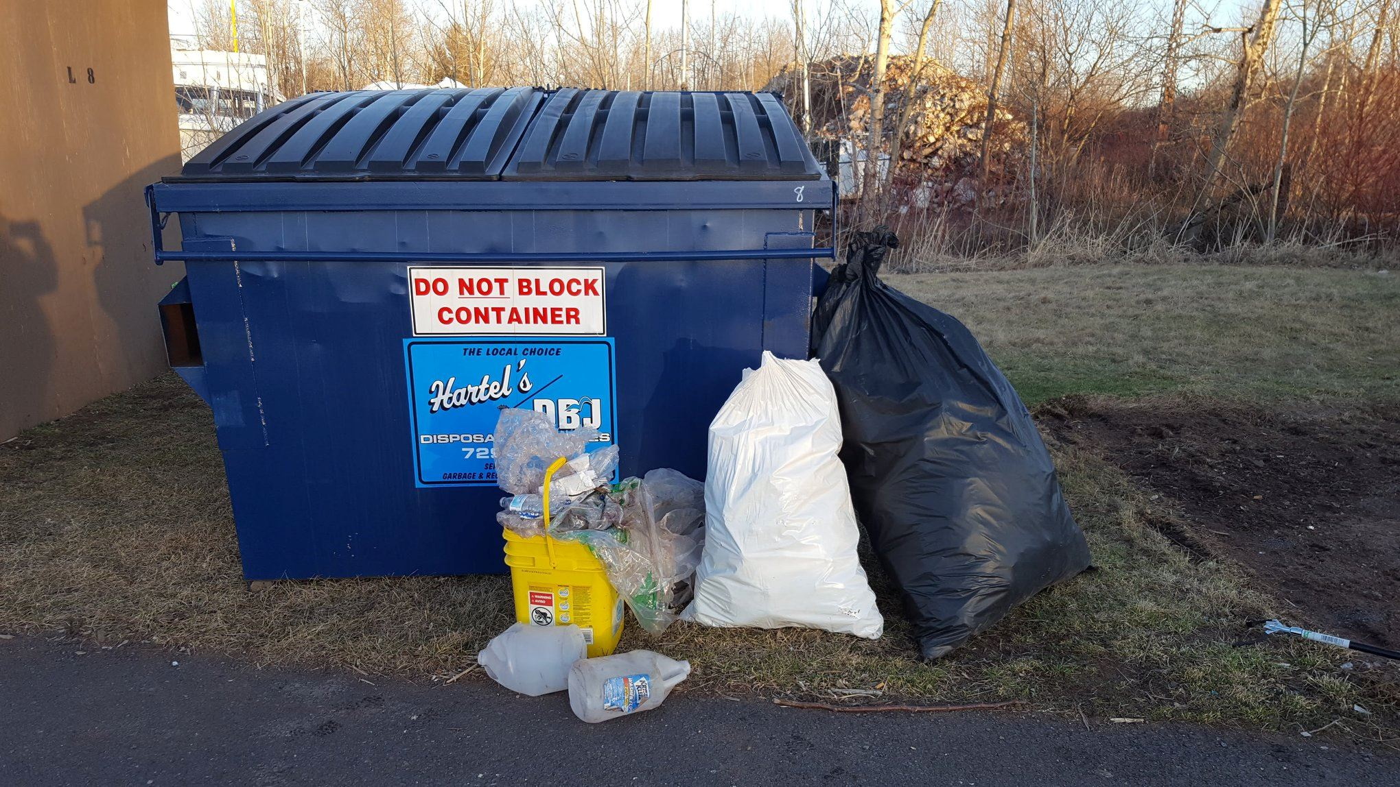 dumpster with bags of trash  collected on Osaugie Trail